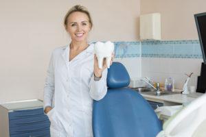 pretty-female-dentist-holding-tooth-model-SVL6WN2