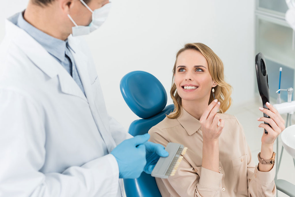 woman-consulting-with-doctor-choosing-tooth-implan-2KJFC4G